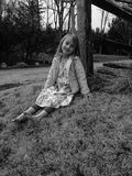 Splendor in the Grass. A Young Girl Sitting Against a Fence Royalty Free Stock Photography