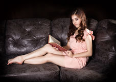 Splendor kobieta w różowym smokingowym obsiadaniu na rzemiennej kanapie czyta książkę