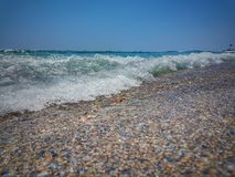 Spletengolven tegen kust De golven die van de Middellandse Zee op de kiezelstenen verpletteren Steen in overzees met golf op zons Stock Afbeelding
