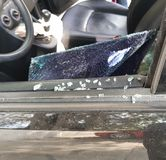 Broken car window glass. With splinters of glass in the door and in the seat inside the vehicle shot glass, automobile insurance coverage, risk and loss stock photos