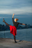 Split of ballet dancer near river. Beautiful blond young woman with black and red costume doing the splits near water royalty free stock photo