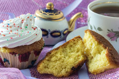 Split biscuit muffin and muffin, decorated with whipped protein cream, on the background cup of  tea  and teapot Royalty Free Stock Photos