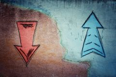 Split concrete wall cracked in the middle and arrows going in two different ways royalty free stock photos