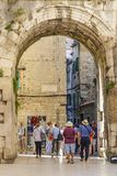 SPLIT, CROATIA, OCTOBER 01, 2017: Tourist walking under the entrance arch leading to the old part of the Split town. royalty free stock photos