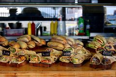 Split, Croatia - 4 22 2019: Street food. Fast food various wraps and sandwiches displayed in a street window of a shop on wooden trays. Urban lifestyle concept stock photo