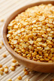 Split dried yellow peas. Wooden bowl full of split dried yellow peas Royalty Free Stock Image