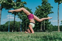 Split on elbows in the park on a grass in a sunny day. Gymnast doing split on elbows in the park on a grass in a sunny day Stock Photos