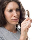 Split ends and damaged hair. Upset angry woman checking split ends on her damaged messy hair, hair care concept Stock Images