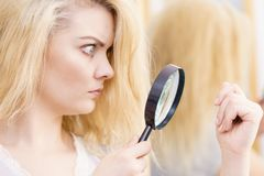 Woman magnifying her split ends hair stock photo