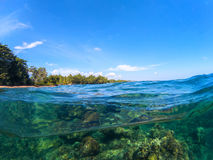 Split landscape with sea and sky. Split photo with tropical island and underwater coral reef. Royalty Free Stock Image