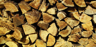 Split logs for fireplace. Neatly stacked pile of split logs for use as firewood.  End cuts and wood grain is visible.  Bark and rough splinters add texture Stock Image