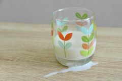 Don`t cry over split milk. Split milk on the wooden table and some in a glass Stock Images