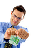 Split the money. Angry businessman tearing money in two in foreground Royalty Free Stock Image
