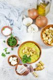 Split pea soup in rustic bowl decorated with fresh green leaves,. Garlic, onion and slices of lard Royalty Free Stock Image