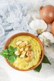 Split pea soup in rustic bowl decorated with fresh green leaves,. Garlic, onion and slices of lard Stock Images