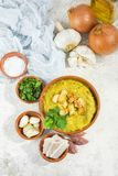 Split pea soup in rustic bowl decorated with fresh green leaves,. Garlic, onion and slices of lard Stock Photo