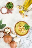 Split pea soup in rustic bowl decorated with fresh green leaves,. Garlic, onion and slices of lard Stock Image