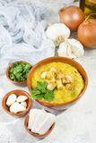 Split pea soup in rustic bowl decorated with fresh green leaves,. Garlic, onion and slices of lard Royalty Free Stock Images