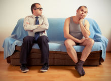 Split personality. Man with split personality sitting on a couch Royalty Free Stock Image