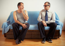 Split personality. Man with split personality sitting on a couch Royalty Free Stock Photo