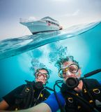 Split photography of yacht, woman and man diver. Split photography of safari yacht, women and men diver exploring coral reef. Underwater fauna, flora and marine royalty free stock photos