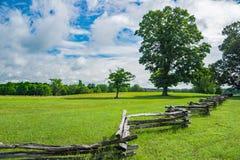 Split Rail Fence in a Field on a Beautiful Spring Day. A split rail fence in a field on clouds and blue skies located Appomattox County, VA. USA royalty free stock photo