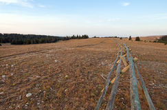 Split Rail Fence next to dirt road at sunrise above Lost Water Canyon USA Stock Image