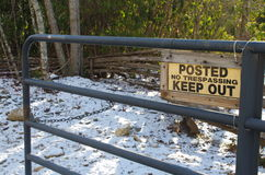 A split rail fence in the souther Appalachian Mountains. Posted keep out, no trespassing sign on a metal gate with a split rail fence in the background in the Stock Image