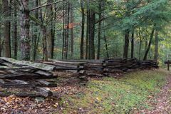 Split rail fence view from side with forest behind on a wet fall day Royalty Free Stock Photo