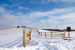 Split Rail Fence Winding Up Snowy Hill. Winding split rail fencing winds up a snow covered hill set against a bright blue wintery sky aswirl with cottony clouds royalty free stock photography