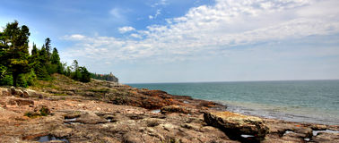 Split Rock Lighthouse. 3 exposure HDR image, looking out into lake superior, and the split rock lighthouse.  Great contrast on the rocky beach, and crystal clear Royalty Free Stock Images