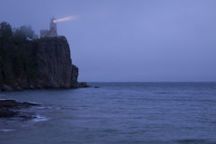 Split Rock Lighthouse Lit. A lighthouse on a cliff casting it's beam of light across the sea Stock Photo