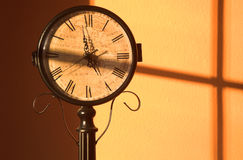 Split Time. A clock face split by a passing shadow Stock Photography