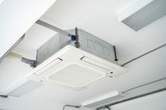 Air condition unit hanging on the ceiling. Split type air condition unit hanging on the white ceiling royalty free stock images