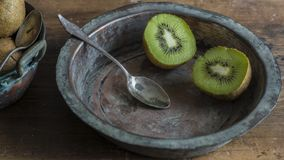 Kiwi fruit on wooden surface. Split up kiwi fruit on wooden surface with weathered copper bowl on black background Royalty Free Stock Photo