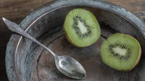 Kiwi fruit on wooden surface. Split up kiwi fruit on wooden surface with weathered copper bowl on black background Stock Images