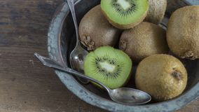 Kiwi fruit on wooden surface. Split up kiwi fruit on wooden surface with weathered copper bowl on black background Stock Photos
