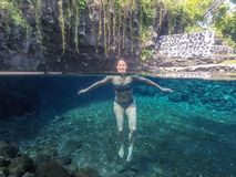 Split view of happy smiling middle aged caucasian female tourist. Swimming in bikini in Piula Cave Pool, Upolu Island, Western Samoa, South Pacific stock photo