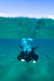 Split view photo with male scuba diver swimming under water.  Royalty Free Stock Photography