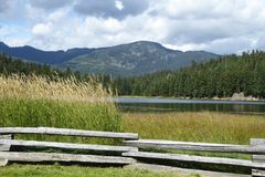 Split wood fence frames a lake and mountain scene. A wood fence surrounds a recreational lake with a foreground of reed grasses and a mountain backdrop in the stock image