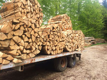 Split wood loaded. Large lengths of split fire wood are bundled in round bales and loaded on a truck in Switzerland stock photography