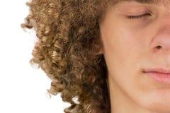 Splited en medio retrato cosechado de un hombre europeo rizado joven con el pelo rizado largo y los ojos cerrados se cierran para imágenes de archivo libres de regalías