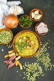 Spliterwtsoep in rustieke die kom met verse groene bladeren, knoflook, ui en plakken van reuzel wordt verfraaid stock afbeelding