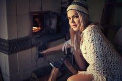 Spliting journaler för kvinna och brinnande trä i ugn hemma Arkivfoto