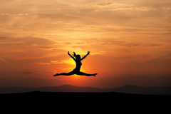 The splits by silhouetted female gymnast Royalty Free Stock Photo