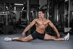 Splits stretches man stretching legs in the gym handsome fitness Royalty Free Stock Photography