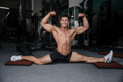 Splits stretches man stretching legs in the gym handsome fitness Stock Photos