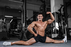 Splits stretches man stretching legs in the gym handsome fitness Royalty Free Stock Photo