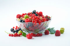Splitted berries in a bowl. Mixed summer splitted berries in a cristal bowl on white Royalty Free Stock Photo