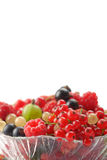 Splitted berries in a bowl. Mixed summer splitted berries in a cristal bowl on white Royalty Free Stock Photography